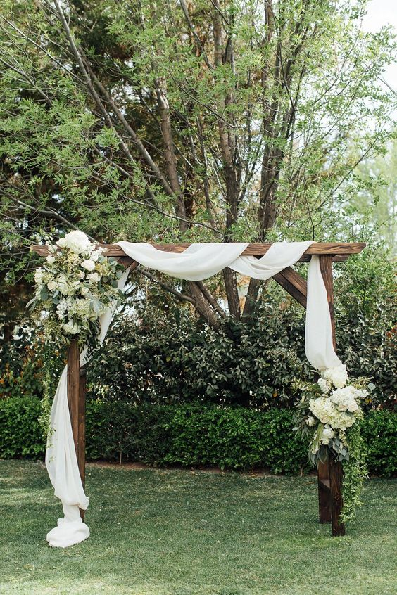 a rustic backyard wedding arch covered with white fabric, with greenery and white blooms is elegant and chic