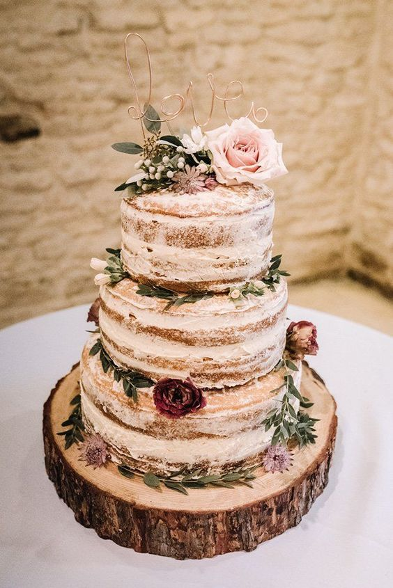 a rustic naked wedding cake with pink and purple blooms and greenery and a wire topper is a yummy piece