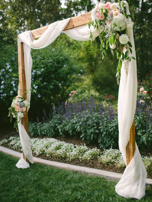 a simple backyard wedding arch decorated with white fabric, with neutral and pastel blooms and greenery is cool