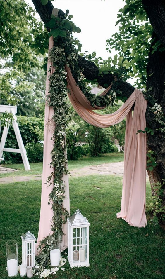 a simple backyard wedding ceremony space with blush fabric on branches, greenery, candles and candle lanterns is cool