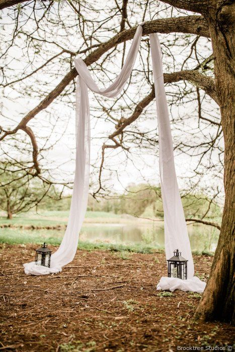 a simple backyard wedding ceremony space with white fabric hanging from the branches, candle lanterns and a gorgeous lake view