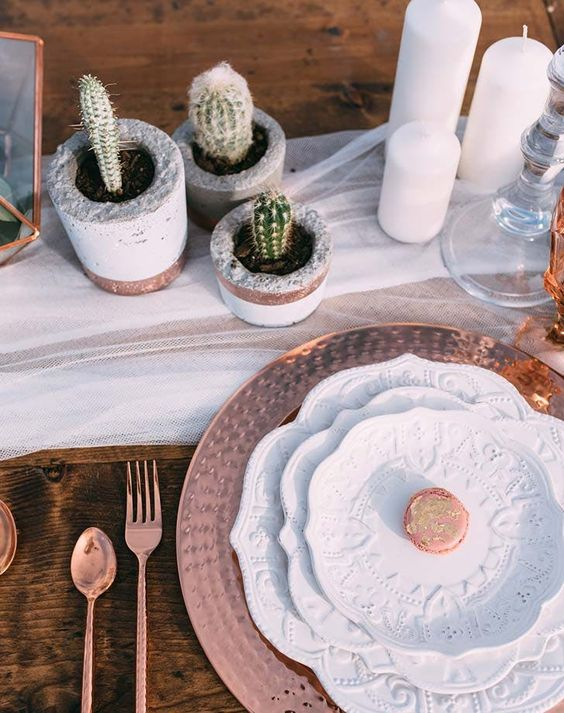 a simple boho chic tablescape with a white runner, patterned plates and chargers, potted cacti, candles and copper cutlery