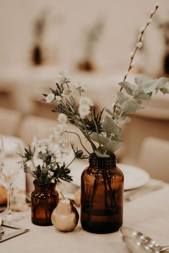 a simple boho wedding centerpiece with apothecary bottles with greenery and white blooms and a gilded pear