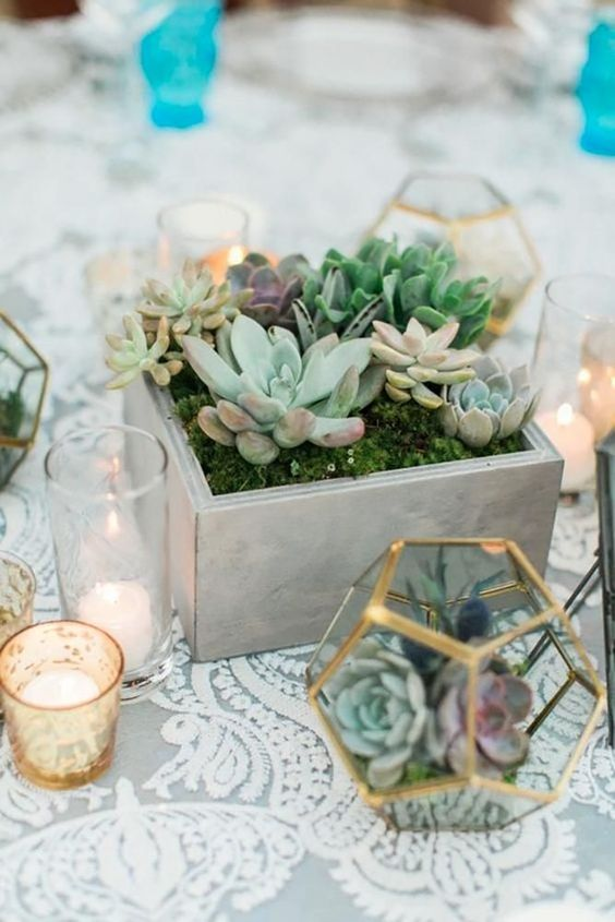 a simple boho wedding centerpiece with succulents planted in a box, candles and terrariums with succulents