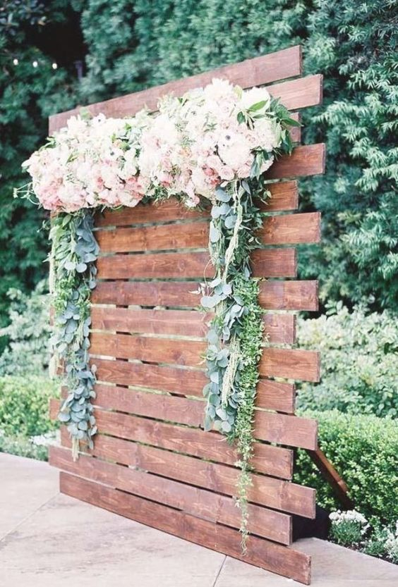 a simple stained wood backdrop with greenery and blush blooms is a lovely idea for a backyard spring or summer wedding
