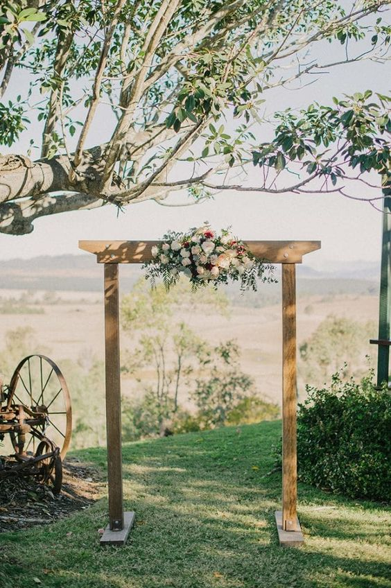 a simple wooden wedding arch with neutral and burgundy blooms and greenery is a lovely idea for a backyard wedding