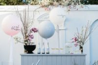 a spring blossom bar with blooming branches, cute balloons and cool drinks for a spring bridal shower