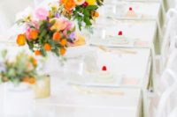 a spring bridal shower tablescape with super colorful florals, gold touches and pastel desserts