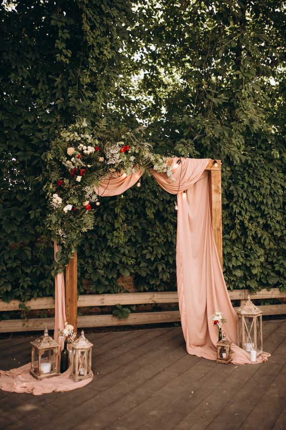 a stylish backyard wedding arch decorated with greenery, white and red blooms and blush fabric, with lights and candle lanterns
