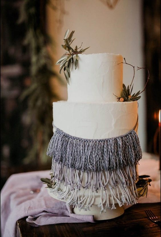 a textural white wedding cake with ombre macrame and some greenery for a spring boho wedding