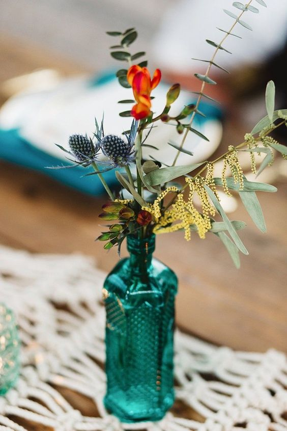 a turquoise bottle with eucalyptus, thistles and blooms is a great boho wedding centerpiece