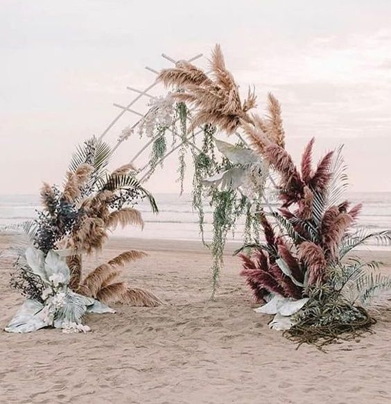 a unique boho beach wedding arch with pale and usual greenery, pampas grass and greenery hanging down