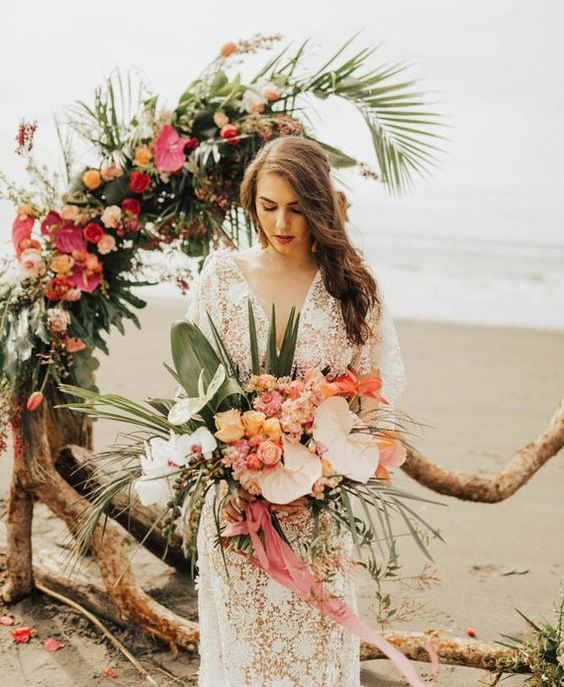 a unique wedding arch of driftwood, tropical leaves and bright tropical blooms is a fantastic idea