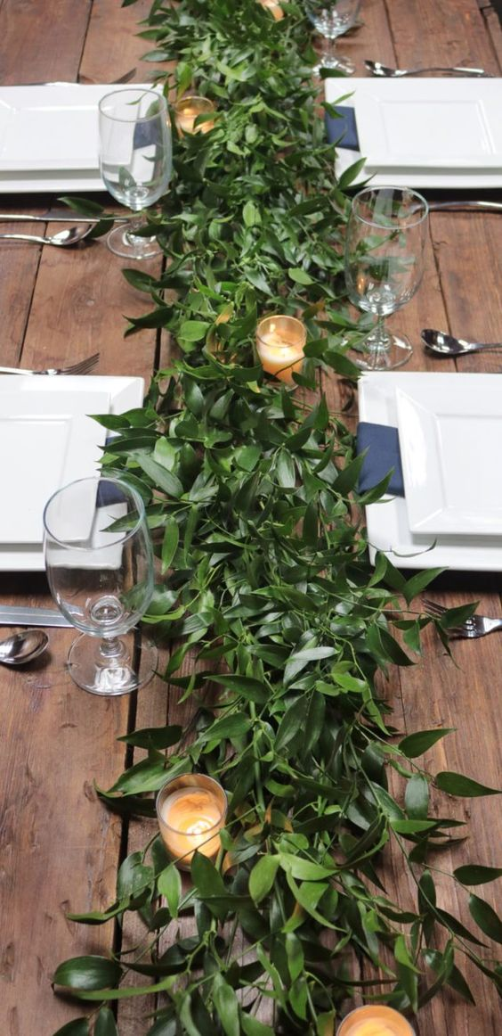 a very lush greenery table runner with candles is a chic idea for any modern wedding, it's very refreshing
