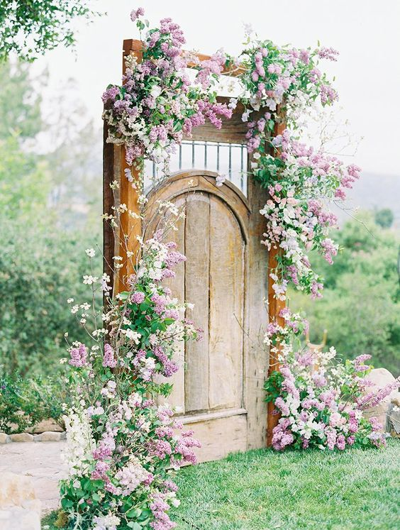 a vintage backyard wedding backdrop of a wooden door and with pink and white blooms and greenery