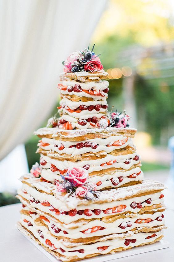 a waffle wedding cake with creamy filling, lots of berries and fresh blooms for a rustic brunch wedding