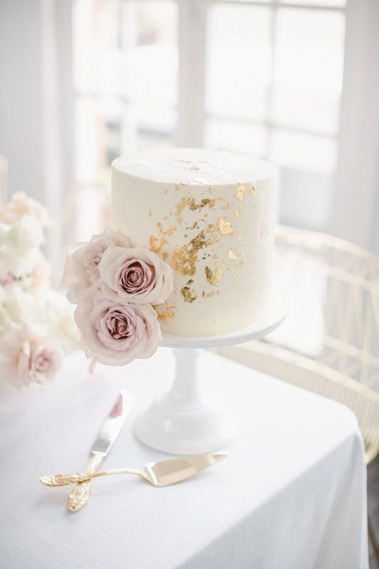 a white bridal shower cake with gold leaf and blush blooms looks very chic and stylish