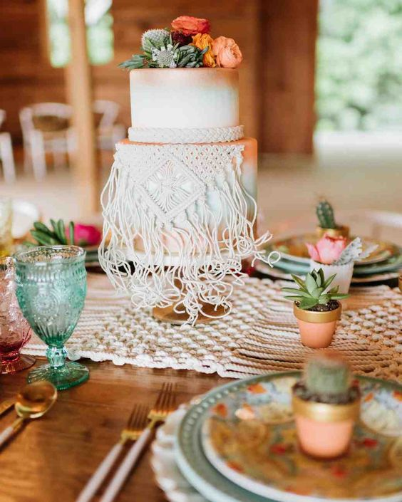 a white gradient wedding cake in white, mint, copper, peachy, with bright blooms and cacti on top and macrame detailing