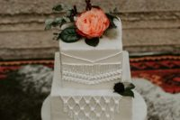 a white square wedding cake with macrame detailing, greenery and a bold fresh bloom on top for a boho wedding