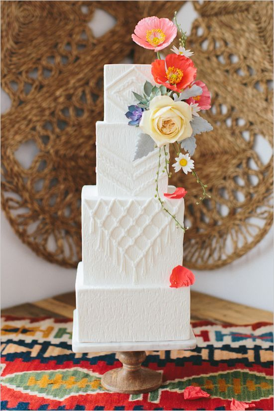 a white textural wedding cake with macrame detailing, pale greenery and super bright blooms on top