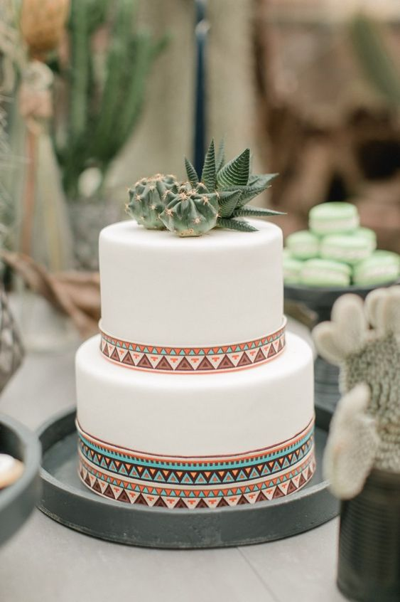 a white wedding cake with bright patterns, cacti and succulents for a boho desert wedding