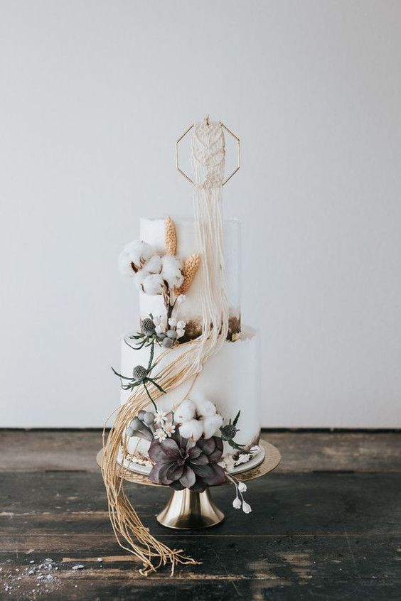 a white wedding cake with cotton, dried succulents, thistles, a hex topper with macrame detailing for a boho wedding