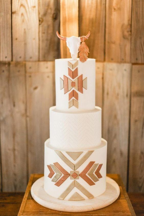 a white wedding cake with geometric patterns, metallic geometric detailing and a sugar skull with a feather on top