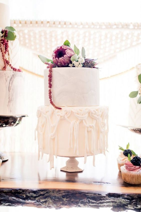 a white wedding cake with sugar macrame decor and a marble tier plus dramatic dark blooms on top