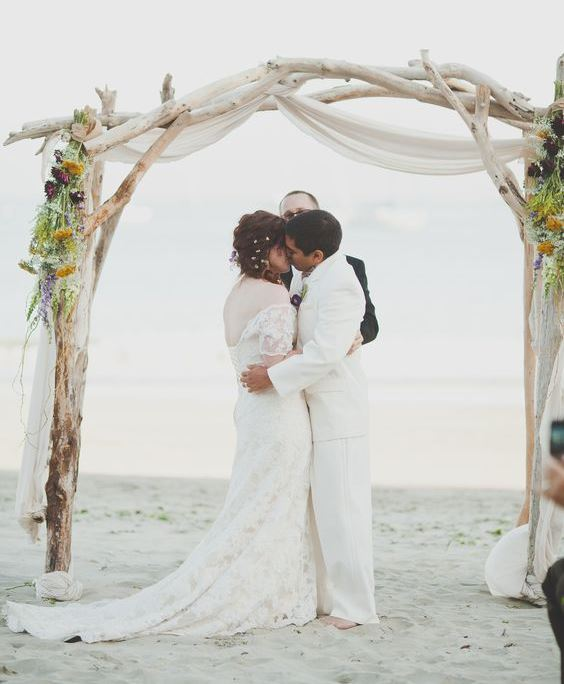 a whitewashed driftwood wedding arch decorated with white fabric, greenery and dried blooms for a coastal wedding