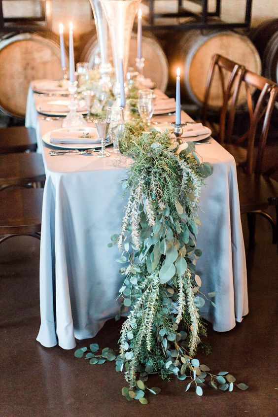 a wild-looking greenery table runner going to the floor and grey canldes plus a greay tablecloth for a chic setup