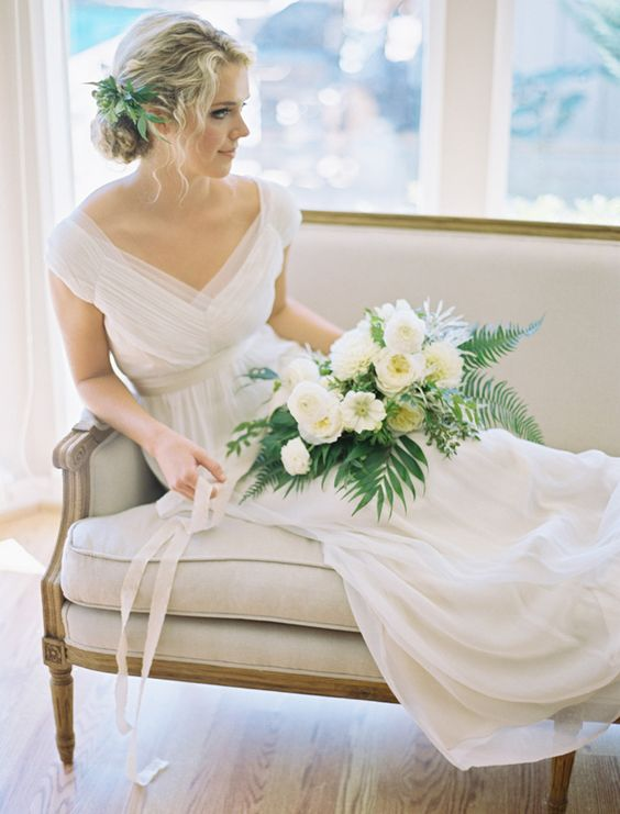 an airy and romantic wedding dress with a deep V neckline, cap sleeves, a draped bodice, an empire waist and a pleated skirt