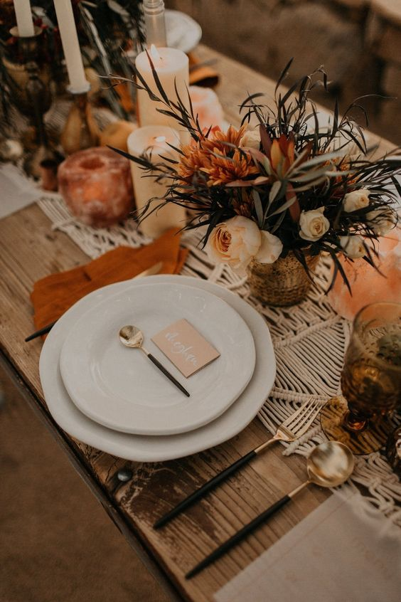 an earthy tone tablescape with a macrame table runner, rusty textiles, a floral centerpiece, candles and dark cutlery