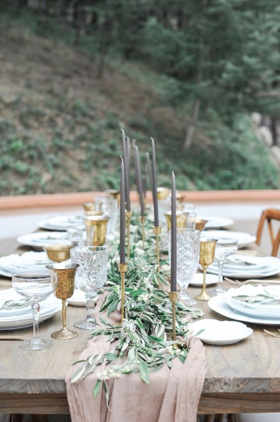 an elegant al fresco tablescape with an olive branch table runner and gold candle holders and grey candles