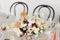 an elegant and fresh spring bridal shower table with a whimsy floral centerpiece, dark cutleryand candles in wooden candle holders