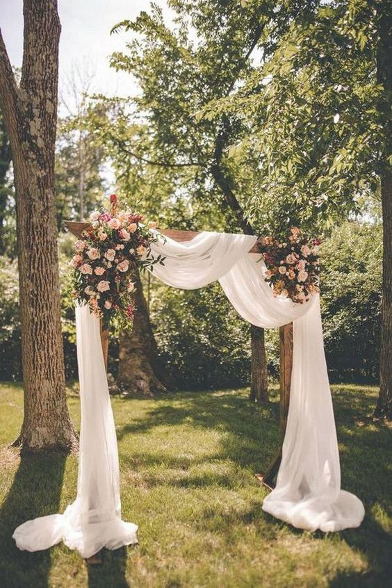 an elegant backyard wedding arch decorated with white fabric, blush blooms and greenery is classics