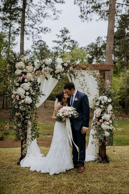 an elegant rustic wedding arch decorated with greenery, white and pastel blooms is a chic idea for a backyard wedding