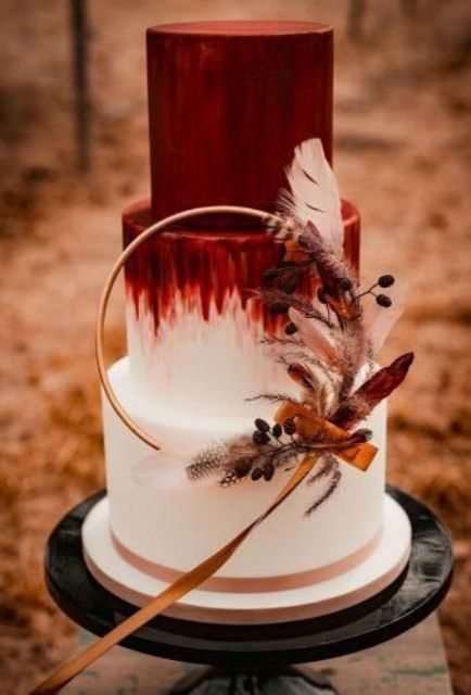an ombre burgundy to white wedding cake with a catchy wreath with berries, feathers, ribbons and a copper base