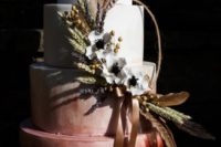 an ombre white to burgundy wedding cake decorated with feathers, spikes, lavender, white blooms and ribbons for a bold boho wedding