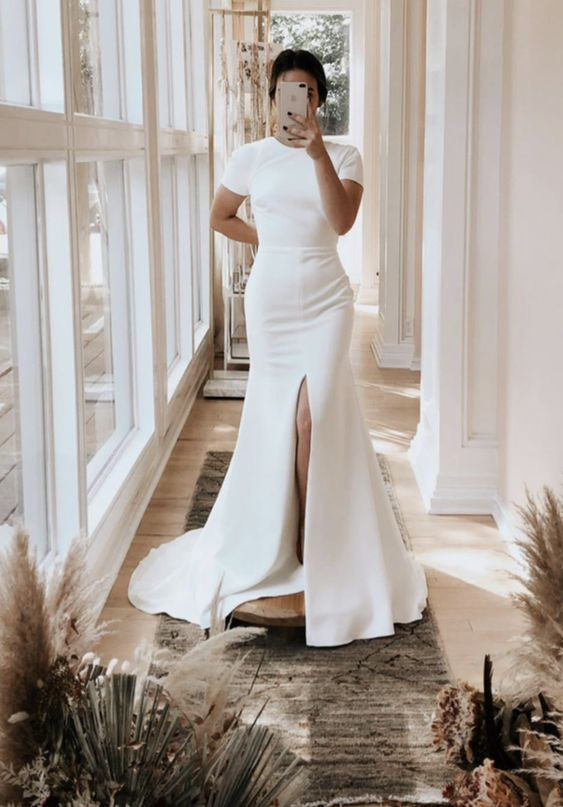 an ultra-modern plain fitting wedding dress with a high neckline, short sleeves, a front slit and a train for a minimalist bride