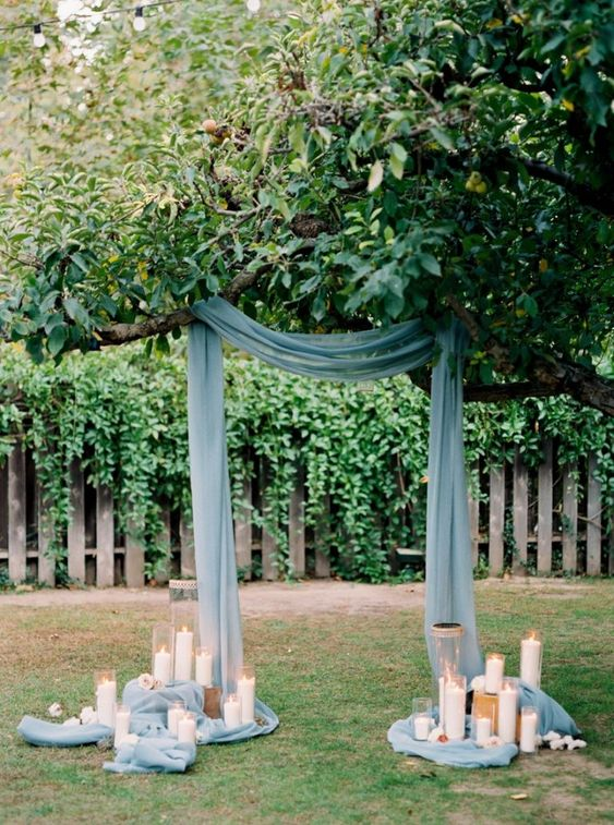 blue fabric hanging from the branches and lots of candle holders to keep it in place is a lovely and easy idea