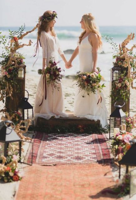 driftwood, candle lanterns, bright and pastel blooms and boho rugs to decorate the boho beach wedding ceremony space