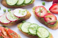 spring crostini with pea pesto and frehs tomatoes, cucumbers and strawberries on top