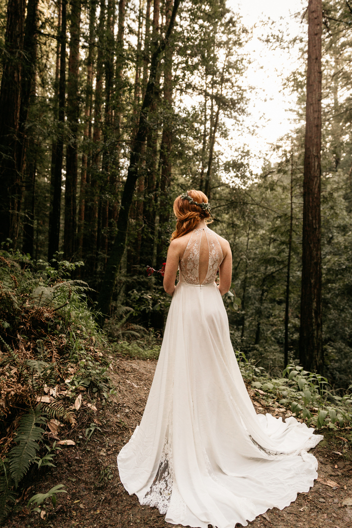 a beautiful A-line wedding dress with a halter neckline, a lace cutout back, a flowy skirt with lace inserts