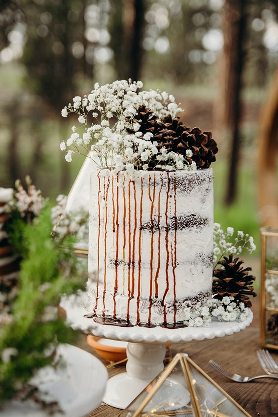 a beautiful and simple semi naked wedding cake with caramel drip, baby's breath and pinecones for a woodland wedding