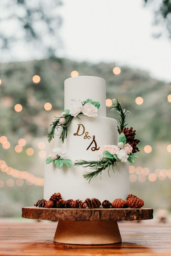 a beautiful and simple woodland wedding cake in white, with pinecones, sugar blooms and greenery