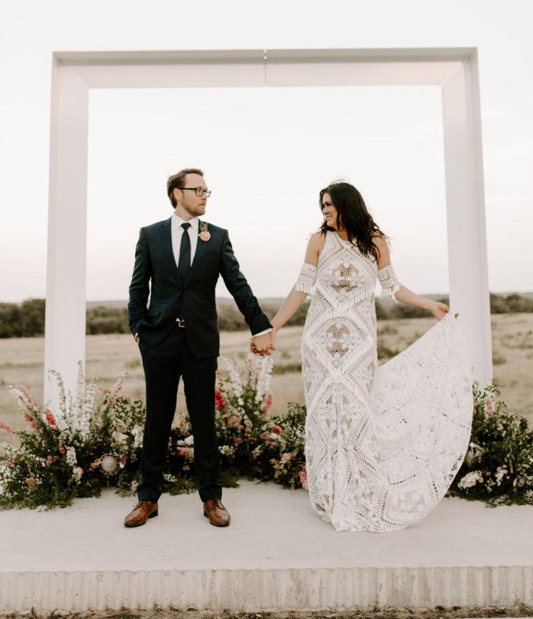 a beautiful boho lace sheath wedding dress with fringe and tassels, tassel arm bracelets, plus a train for a boho bride
