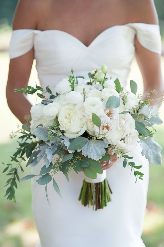 a beautiful wedding bouquet composed of white blooms and pale greenery for a refined look