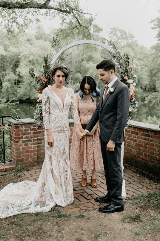 a beautiful white lace sheath wedding dress with an illusion neckline, long sleeves and a train for a summer boho bride