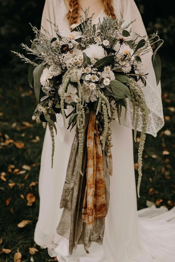 a beautiful woodland wedding bouquet of various types of greenery, white blooms and grasses and colored ribbons