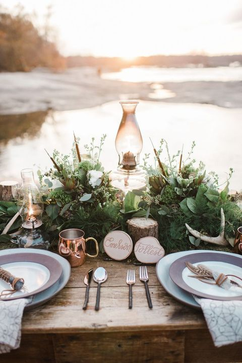 a beautiful woodland wedding tablescape with greenery, feathers, white blooms, a lamp, antlers, wood slices and soem feathers